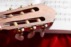 Acoustic guitar and music notes on red velvet fabric, close view of objects Royalty Free Stock Photo
