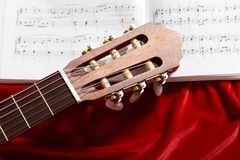 Acoustic guitar and music notes on red velvet fabric, close view of objects Stock Photography