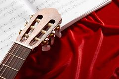Acoustic guitar and music notes on red velvet fabric, close view of objects Royalty Free Stock Image
