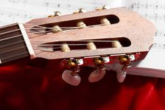 Acoustic guitar and music notes on red velvet fabric, close view of objects Stock Images