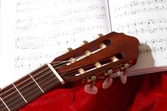 Acoustic guitar and music notes on red velvet fabric, close view of objects Royalty Free Stock Images