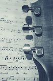 Acoustic guitar and musical score. Acoustic guitar headstock and musical score Stock Images