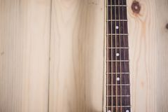 Acoustic guitar neck on wooden background with strings royalty free stock photos