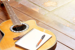 Acoustic guitar with notebook and pen on wood background. Inspiration workspace for relax by acoustic guitar Stock Images