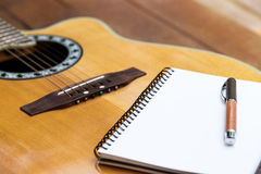 Acoustic guitar with notebook and pen on wood background. Inspiration workspace for relax by acoustic guitar Stock Photo