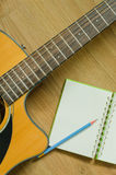 Acoustic guitar and notebook. With wood background Stock Photos