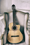 Acoustic guitar on an old armchair Stock Photography