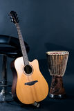 Acoustic guitar with percussion drum. In studio on blue background royalty free stock image