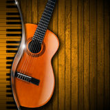 Acoustic Guitar and Piano Wood Background. Acoustic brown guitar and piano against a rustic wood background Royalty Free Stock Photography