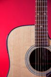 Acoustic Guitar On Red Bk. A guitar isolated against a red background in the vertical format Stock Images