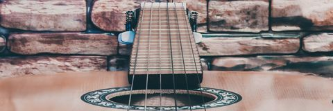 Acoustic guitar on red brick wall background stock photography