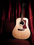 Acoustic Guitar on a Red Stage Royalty Free Stock Photo
