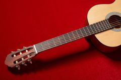 Acoustic guitar on red velvet fabric, closeup object Royalty Free Stock Images