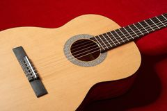 Acoustic guitar on red velvet fabric, closeup object Stock Photo