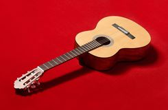 Acoustic guitar on red velvet fabric, closeup object Stock Photos