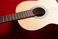 Acoustic guitar on red velvet fabric, closeup object Royalty Free Stock Photography