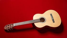 Acoustic guitar on red velvet fabric, closeup object Stock Photography