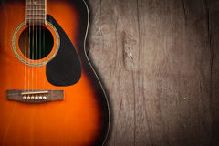 Acoustic guitar resting against a blank grunge background with c. Royalty Free Stock Photo