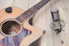 Acoustic guitar resting against a wooden background royalty free stock image