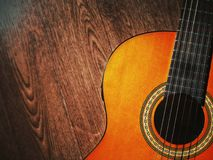 Acoustic guitar resting against a wooden background with copy space Royalty Free Stock Images