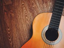 Acoustic guitar resting against a wooden background with copy space. Stock Images