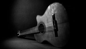 Acoustic guitar resting on the floor. Grayscale, ideal for background Stock Photo