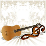 Acoustic guitar rests on the treble clef Stock Photos