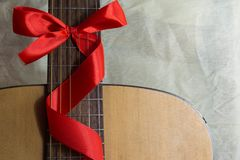 Acoustic guitar with a ribbon bow. Acoustic guitar with lighted garland Royalty Free Stock Photos