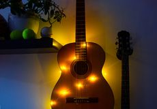 Acoustic guitar in the room hanging on the wall on a rack with a garland, room interior , home hobby. Acoustic guitar in the room hanging on the wall on a rack royalty free stock photos