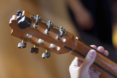 Acoustic guitar's fretboard and young male's hand Stock Photography