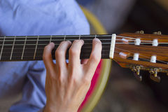 Acoustic guitar's fretboard and young male's hand Royalty Free Stock Photography