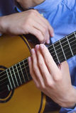 Acoustic guitar's fretboard and young male's hands. Close view of acoustic guitar's fretboard and young male's hands on it Stock Images