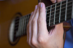 Acoustic guitar's fretboard and young male's hands. Close view of acoustic guitar's fretboard and young male's hands on it Stock Image