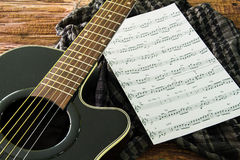 Acoustic guitar and sheet musical notes on the table. Stock Image