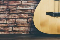 Acoustic guitar stands on a brick wall background. royalty free stock photography