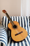 Acoustic guitar on a striped couch Royalty Free Stock Images