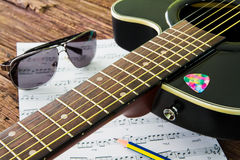 Acoustic guitar, sunglasses and sheet musical notes on the table Royalty Free Stock Images