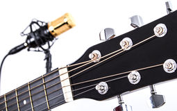 Acoustic Guitar Tuners with Gold Condenser Microphone in Background. Closeup view showing the string tuners of an acoustic guitar with a gold and black colored Royalty Free Stock Photo
