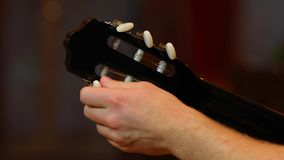 Acoustic Guitar Tuning. Tuning an acoustic guitar ina room stock video footage