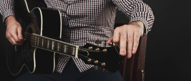 Acoustic guitar tuning and playing close up. In studio Royalty Free Stock Image