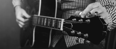 Acoustic guitar tuning and playing close up. In studio Stock Photography