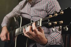Acoustic guitar tuning and playing close up. In studio Stock Image