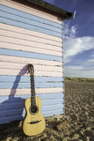Acoustic guitar on vacation. Parlour-sized classical acoustic guitar resting against a beach hut painted in pastel pink and blue. Symbolic of vacation Stock Photography