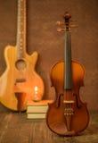 Acoustic guitar,violin,book Stock Photos