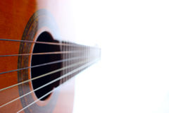 Acoustic guitar on the white background. Classic acoustic guitar at weird and unusual perspective closeup. Six strings free frets sound hole and soundboard Stock Photos