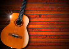 Acoustic Guitar on Wood Background. Acoustic brown guitar against a rustic wood background Royalty Free Stock Photography