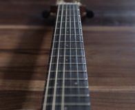 Acoustic guitar on wooden surface with vintage tone. Frets of acoustic guitar on wooden surface with vintage tone royalty free stock photography