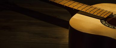 Acoustic guitar on a wooden table lit by a ray of light. Side view stock image