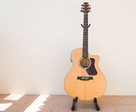 Acoustic guitar. Wooden acoustic guitar with white wall stock photography
