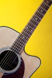 Acoustic Guitar On Yellow Bk. A guitar isolated against a yellow background in the vertical format Royalty Free Stock Photography